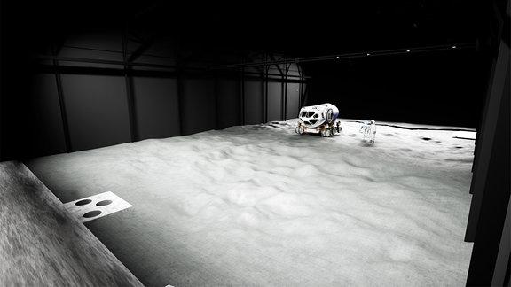 Grafik: So soll die Luna-Trainingshalle in Köln aussehen, wenn sie fertig gebaut ist. Zu sehen ist eine schwarze Halle mit weißem Staub auf dem Boden. In der Ecke steht ein Fahrzeug.
