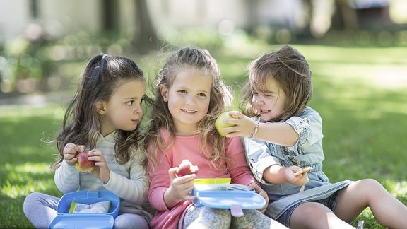 Kleine Mädchen teilen ihr Frühstück
