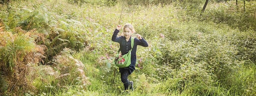 d5480e056c8ed2 Ein Mädchen läuft über eine Wiese auf einer Waldlichtung.