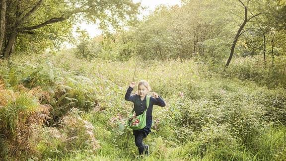 Ein Mädchen läuft über eine Wiese auf einer Waldlichtung.
