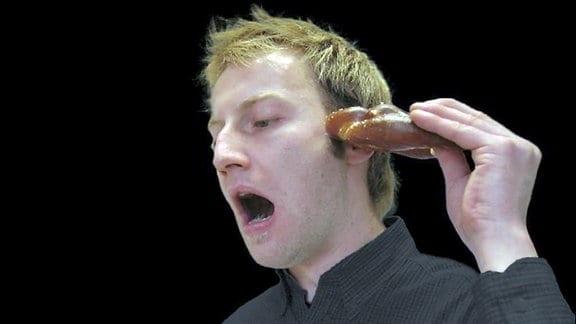 Mann führt Brezel zum Ohr