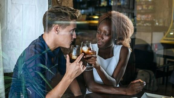 Ein junger Mann und eine junge Frau stoßen mit ihren Gläsern in einer Bar an