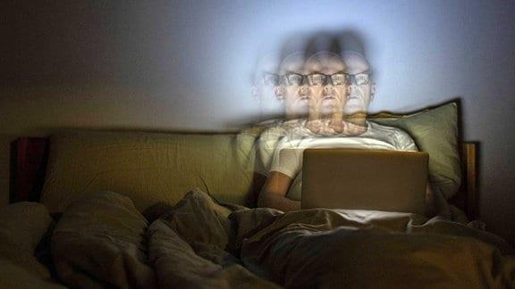 Mann liegt mit einem Laptop im Bett