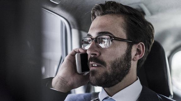 Ein Geschäftsmann telefoniert im Auto.