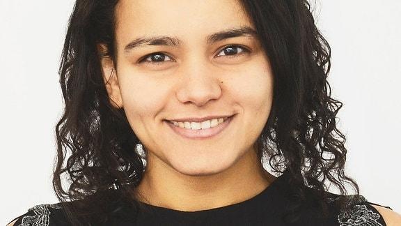 Porträt einer jungen Frau mit dunklen, gelockten Haaren und einem dunklen Oberteil.