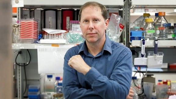 Ein Mann im blauen Oberhemd sitzt in einem Labor, hinter ihm stehen Aktenordner, Ampullen, und Plastikflaschen im Regal.