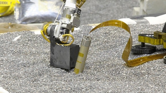 Eine Robotersonde gräbt sich in die Erde.