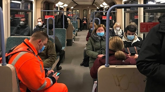 Menschen sitzen in Zeiten der Coronapandemie mit medizinischen Mundmasken in einer vollen S-Bahn