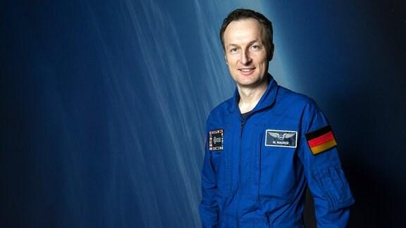 Matthias Maurer in blauem ESA-Tainings-Anzug vor blauem Hintergrund
