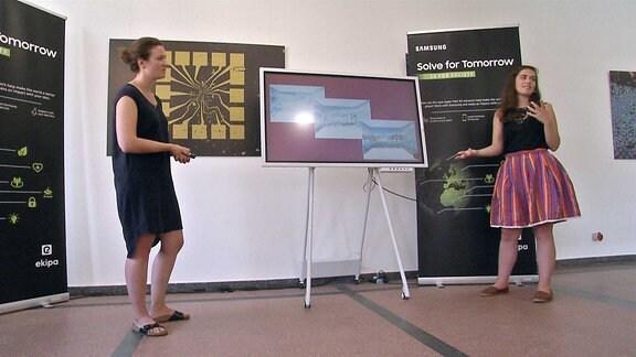 Zwei Frauen neben einem Bildschirm.