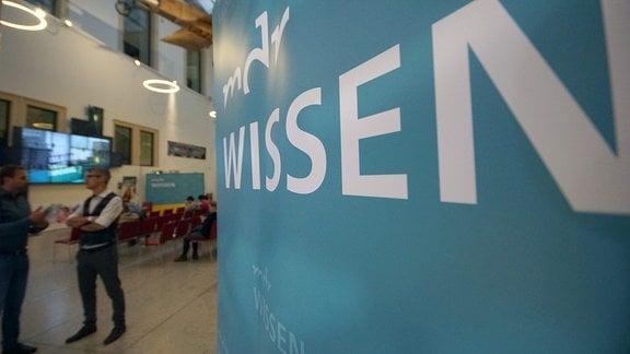 Ein Plakat mit dem Logo von mdr Wissen in einem Veranstaltungssaal.