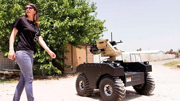 Neben einer Frau mit Sonnenbrille steht ein motorisiertes Gefährt mit einem Maschinengewehr.