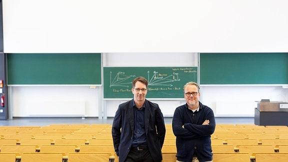 Zwei Männer stehen angelehnt an eine Sitzreihe in einem Unihörsaal. Im Hintergrund hängen Tafeln an der Wand.