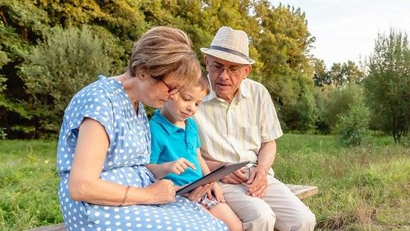 Kind erklärt Großeltern die Handhabung eines Tablet-PCs