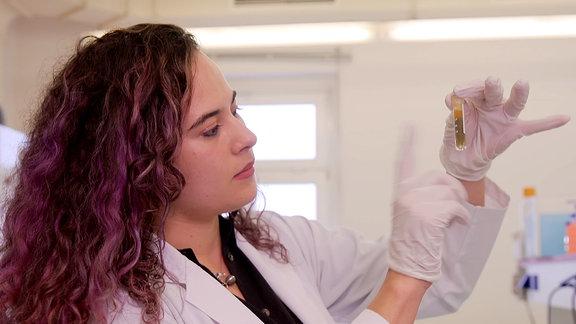 Eine junge Frau im weißen Kittel schaut sich im Labor Exkremente an.