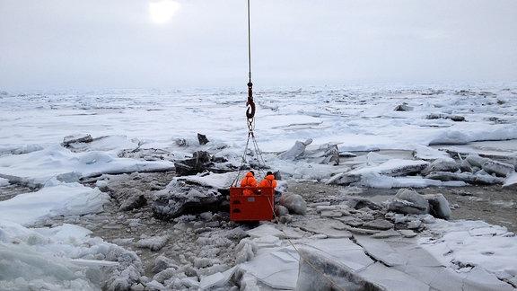 Zwei Forscher lassen sich per Kran von dem Eisbrecher Polarstern auf dem Eis absetzen, um Probenmaterial zu sammeln