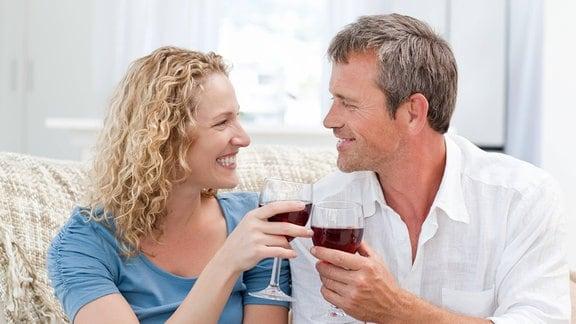 Paar stößt lächelnd mit Rotwein an