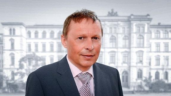 Ein Mann schaut in die Kamera, im Hintergrund ein historisches Gebäude
