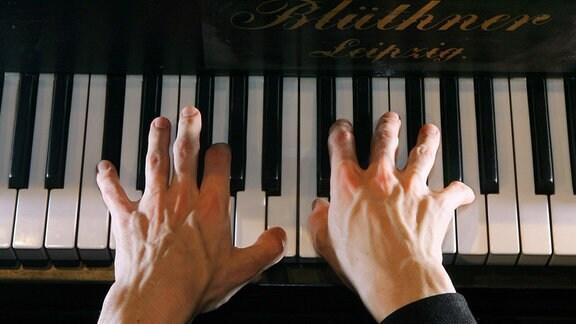 Zwei Hände auf den Tasten eines Pianos