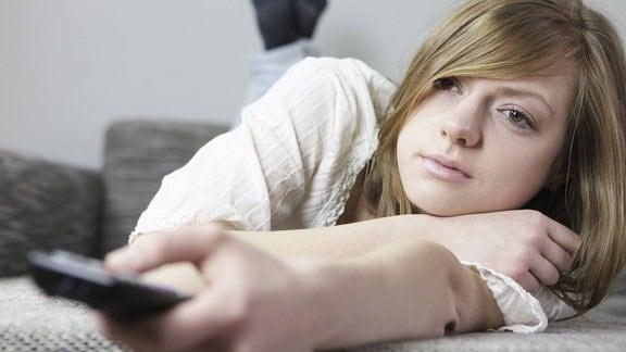 Junge Frau auf dem Sofa mit Fernbedienung in der Hand
