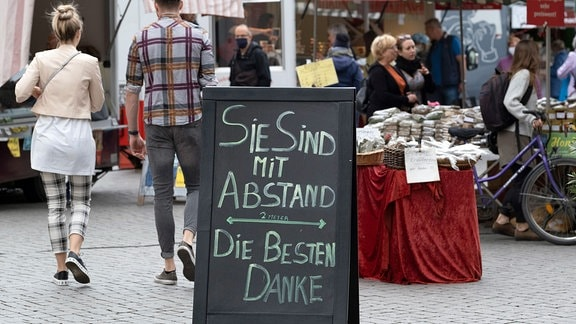 Hinweisschild zum Abstandhalten auf dem Wochenmarkt auf dem Richard-Wagner-Platz in Leipzig.