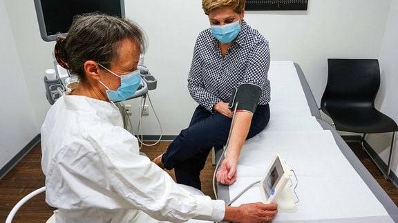Ärztin misst bei einer Patientin den Blutdruck.