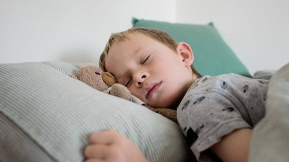 Schlafender Junge mit Teddybär im Bett