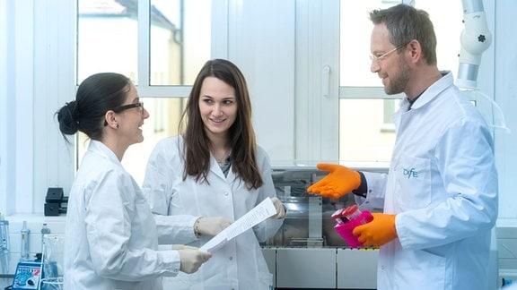 Drei Wissenschaftler mit weißen Kitteln, links zwei Frauen, rechts ein Mann, stehen in einem Labor.