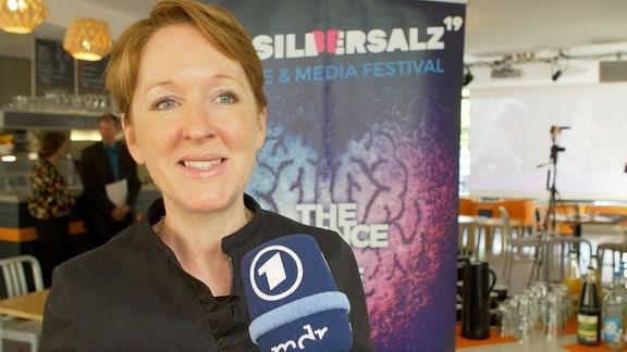 Eine Frau spricht in ein Mikrofon. Im Hintergrund hängt ein Banner mit der Aufschrift Silbersalz-Festival.