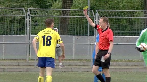 Der Schiedsrichter zeigt dem Spieler die gelbe Karte.