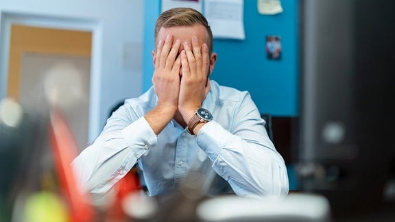Geschäftsmann sitzt an Schreibtisch und verdeckt sein Gesicht mit den Händen.