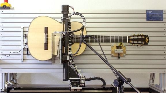 Eine Gitarre ist zum Testen an eine Wand montiert