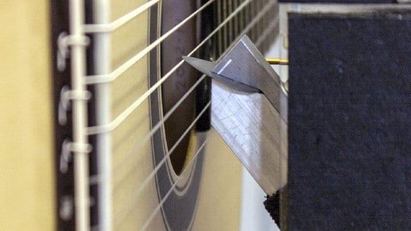 Ein Stahlfinger zupft an einer Gitarrensaite