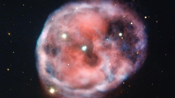 Der unheimliche Totenkopfnebel, der mit dem Very Large Telescope (VLT) der ESO in verblüffender Detailgenauigkeit aufgenommen wurde, wird auf diesem neuen Bild in wunderschönen Rosa- und Rottönen dargestellt. Dieser planetarische Nebel, auch bekannt als NGC 246, ist der erste, von dem bekannt ist, dass er mit einem Paar eng verbundener Sterne assoziiert ist, die von einem dritten äußeren Stern umkreist werden
