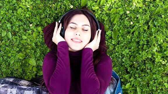 Eine junge Frau liegt mit Kopfhörern auf einer Wiese
