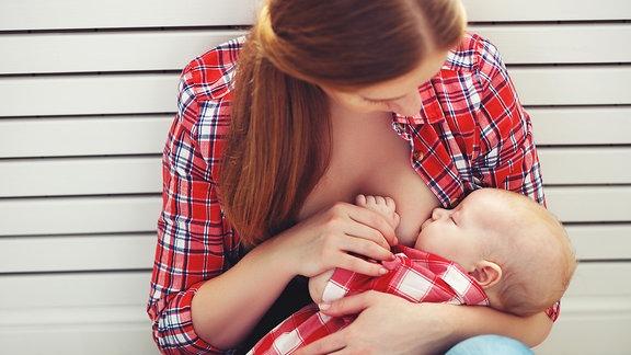 Eine junge Frau stillt ein Baby