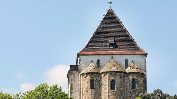 Eine Kapelle steht auf einem Felsen, unterhalb des Gebäudes  erstreckt sich Wald