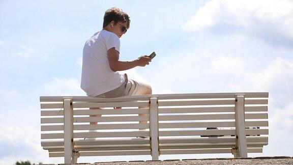 Ein Junger Mann sitzt auf der Lehne einer Parkbank und schaut auf sein Mobiltelefon.