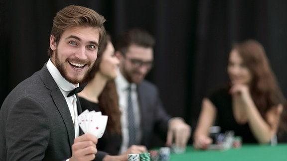 Spieler mit Karten in der Hand schaut lachend zur Kamera.
