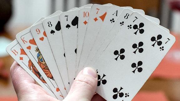 Ein Skatspieler hält Spielkarten in der Hand.