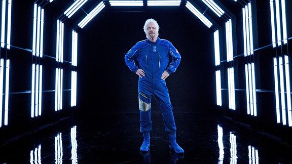 Ein Mann in einem blauen Ganzkörperanzug steht in einem Tunnel.