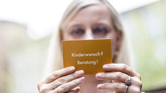 Frau schaut auf eine Karte mit der Aufschrift ''Kinderwunsch Beratung''.