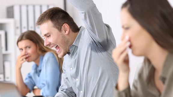 Ein Mann hebt einen Arm, an der Achsel ist ein dunkler Fleck auf dem Hemd zu sehen, zwei Frauen halten sich die Nase zu