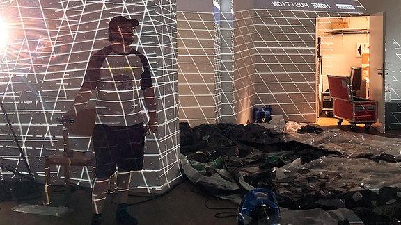 Ein Mann in einem dunklen Raum, weiße Linien sind an die Wände projiziert.