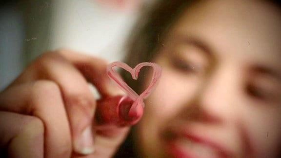 Eine Frau malt mit einem Lippenstift ein Herz an eine Scheibe.