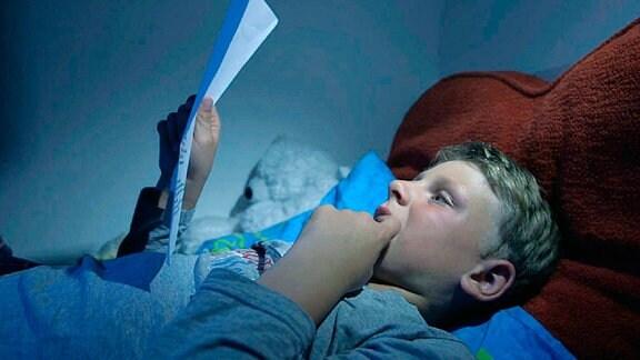 Ein Junge liegt im Bett und liest.