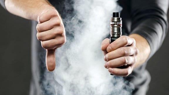 Dampf aus einer E-Zigarette - Ein Mann zeigt dabei den Daumen nach unten.