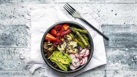 Vegetarisches Gericht mit Spargel, Avocado, Pilzen, Radieschen und Erdbeeren auf einem Teller