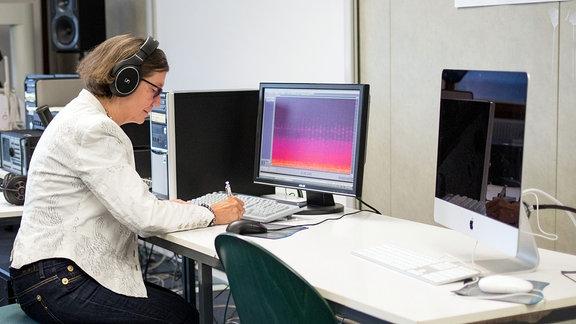 Frau sitzt mit Kopfhörern am Computer
