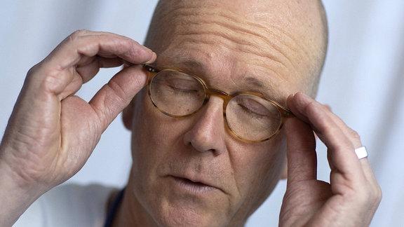 Mann greift mit geschlossenen Augen seine Brille
